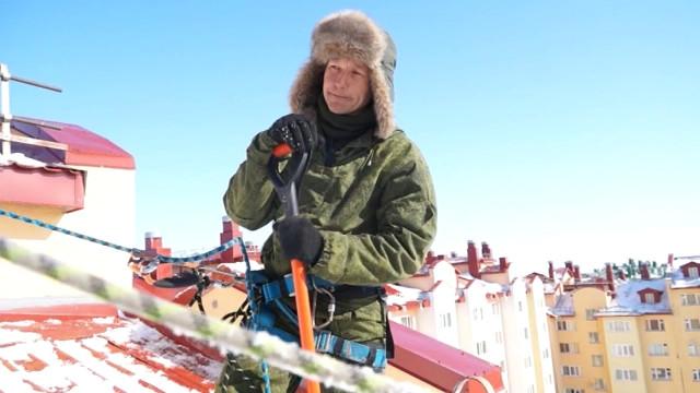 Чистить кровлю отснега коммунальщикам помогают промышленные альпинисты.
